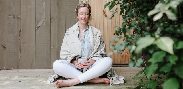 A woman sitting cross-legged with her eyes closed meditating on her deck, while holding a mug of coffee.