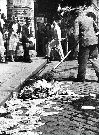 A man sweeping Hungarian pengő currency off of a street circa 1946.  The pengő suffered the worst hyperinflation in history. Credit: Mizerák István via Wiki