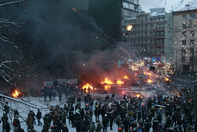 Pro-European protesters set off fireworks and burn tyres during a rally in central Kiev