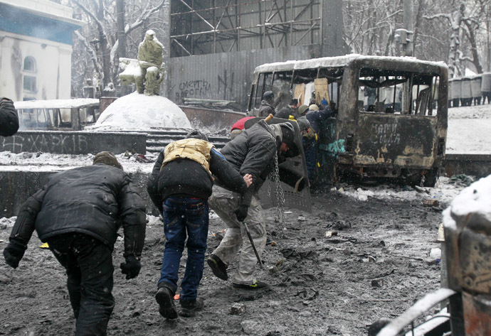 Pro-European protesters take cover behind a burnt bus during clashes with riot police in Kiev January 22, 2014. (Reuters/Gleb Garanich)
