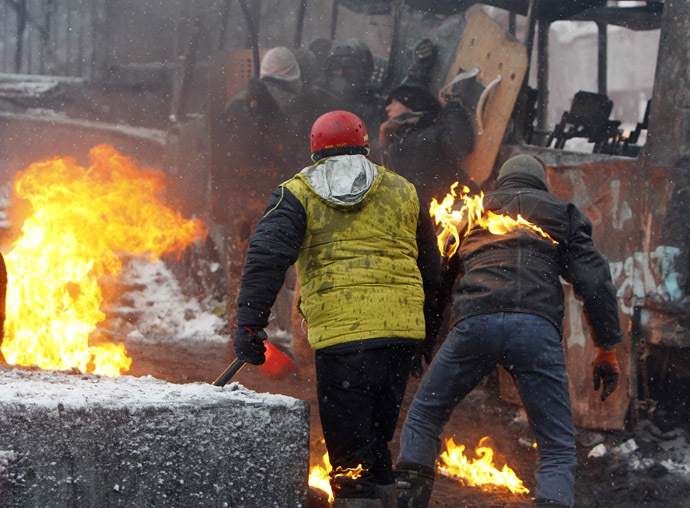 Pro-European protesters take cover behind a burnt bus, with a demonstrator seen on fire, during clashes with riot police in Kiev January 22, 2014 (Reuters/Gleb Garanich)
