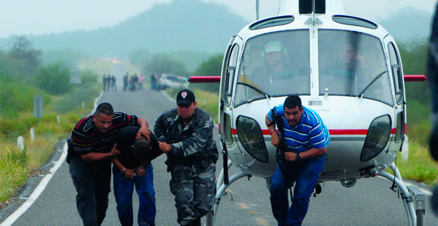 Police take a suspected drug trafficker off a helicopter in the state of Sonora. Credit: knightfoundation / Flickr