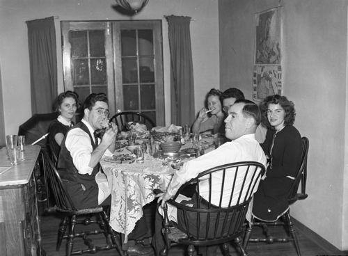 Six people sitting around dinner table
