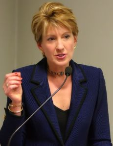 Carly_Fiorina_in_dark blue talking into a mic.