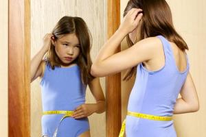 Lookism? Little girl with tape measure around her waist looks into mirror.