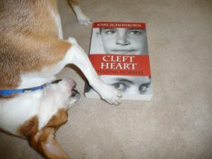 Small dog named Monte about to chew on  book abt cleft lip.
