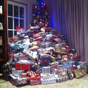 Xmas tree swamped by too many gifts showing Materialism, Consumerism.Bullying & Overindulgence & Bullying.