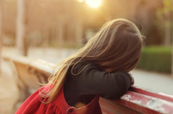 Little girl with long hair, rests on a bench in the park, turned away from the camera. Photos backlit.
