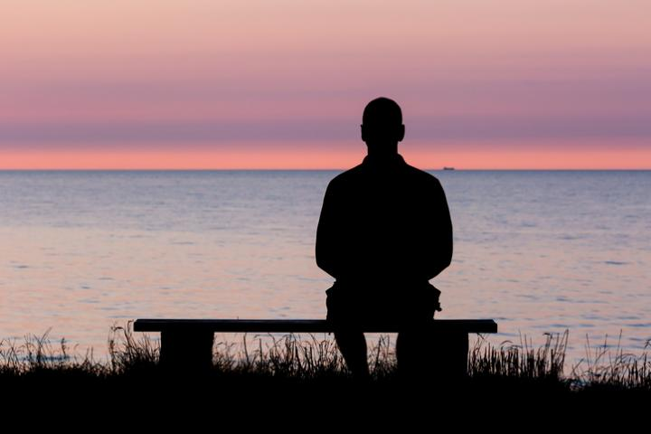 Silhouette of male person against a colorful horizon.