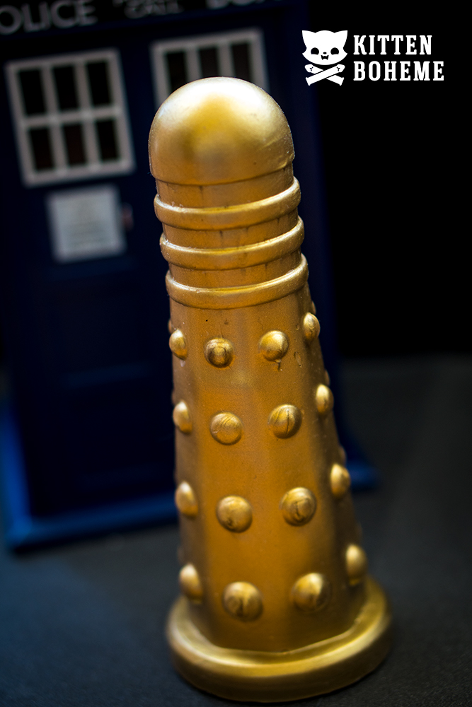 Geeky Sex Toys Doctor Screw Dildek Silicone Doctor Who Dalek Themed Gold Dildo Standing in front of a Tardis
