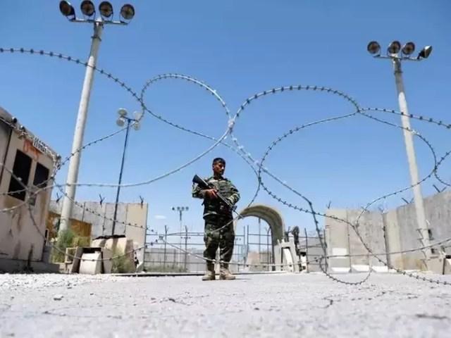 Afghan National Army soldier stands guard at Bagram US air base gate on day of troop departure.