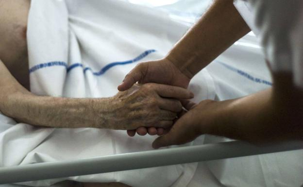 A health worker cares for a terminally ill patient in a file image.