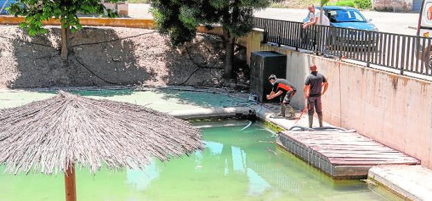 Operators install the pumps to drain the stagnant water on the Coy river beach, yesterday.