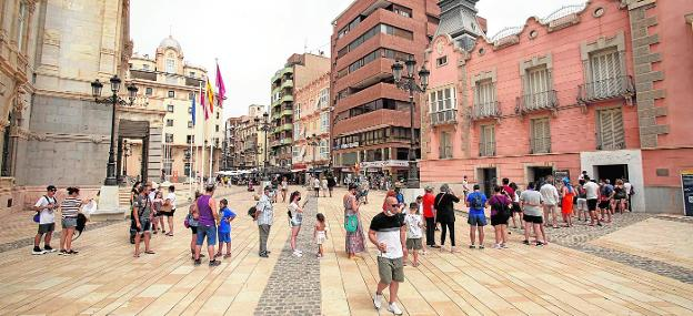 More than thirty people, including entire families, queue to visit the Museum of the Roman Theater.  In the background, the terraces of two bars in the Plaza del Ayuntamiento full of customers at mid-morning.
