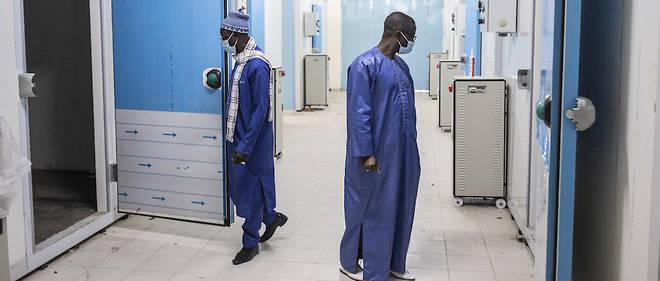 Ousseynou Badiane, responsable du programme de vaccination du Senegal, ouvre la porte d'une chambre froide nouvellement construite a l'hopital Fann de Dakar le 22 janvier 2021. Ces chambres froides permettront de stocker le stock de vaccins contre le Covid-19 du pays.