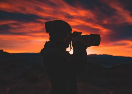 Person holding a camera at sunset