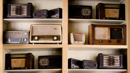 Old analog radios on a bookshelf