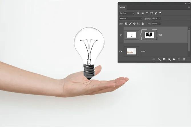 Слой Photoshop замаскированный изображением руки и лампочки