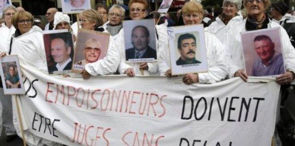 Des manifestants brandissent des portraits de victimes de l'amiante, en février 2013 à Paris © Reuters