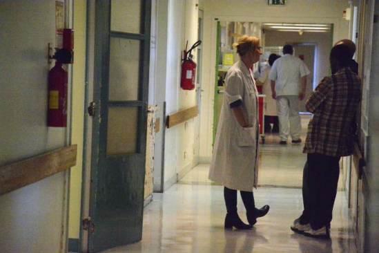Dans les couloirs du service d'hospitalisation de jour, un médecin du service discute avec la famille d'un patient.