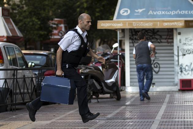 Livraison d'argent dans une banque d'Athènes, dimanche 28 juin.