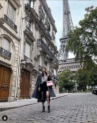 Luxury fashion influencer Mel in Melbourne walking a Paris street with the Eiffel Towerin the background and holding a Hermes bag