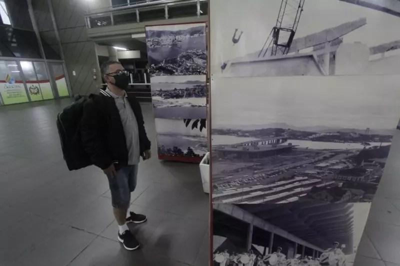 Turista olhando exposição de fotos e artes do Rita Maria
