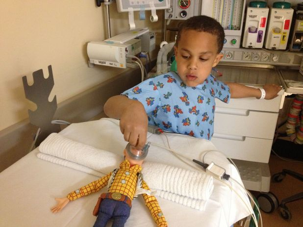 A boy administers anesthetic to a doll