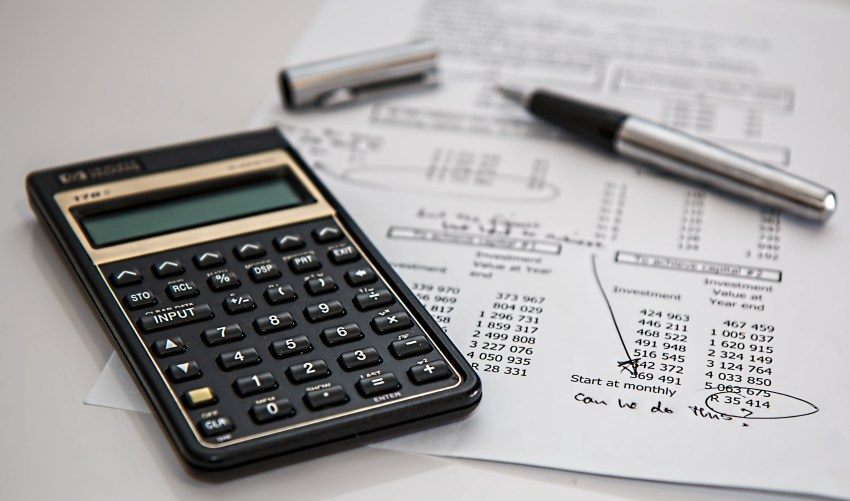 A calculator sits on top of financial statements.