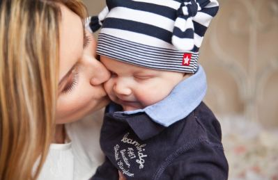 Woman in White Shirt Kissing Baby With Black and White Stripe Knit Cap