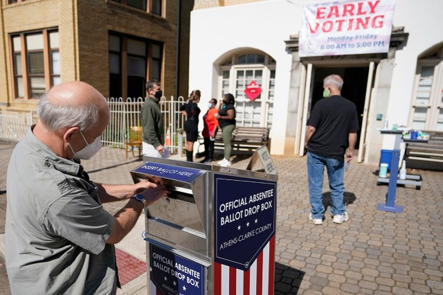 A voter submits a ballot in an official drop box.