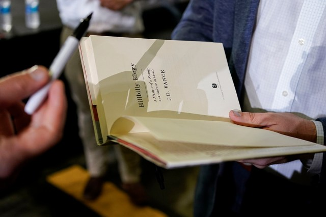 """JD Vance, the venture capitalist and author of """"Hillbilly Elegy,"""" autographs a book after a rally."""