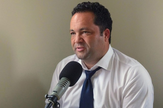 Ben Jealous speaks into a microphone while wearing a white dress shirt and blue tie.