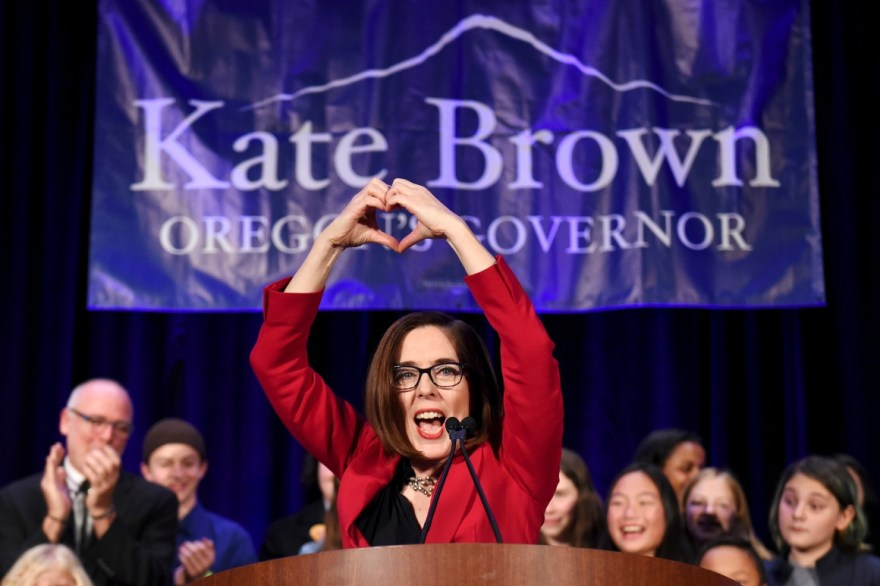 Oregon Gov. Kate Brown makes a heart shape with her hands.