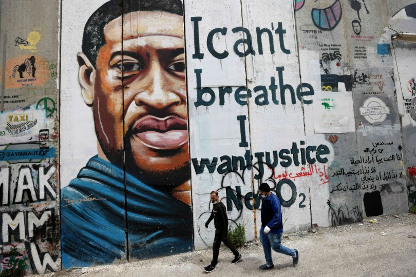 Les gens passent devant une peinture murale montrant le visage de George Floyd peint sur une section de la barrière de séparation controversée d'Israël dans la ville de Bethléem en Cisjordanie occupée.