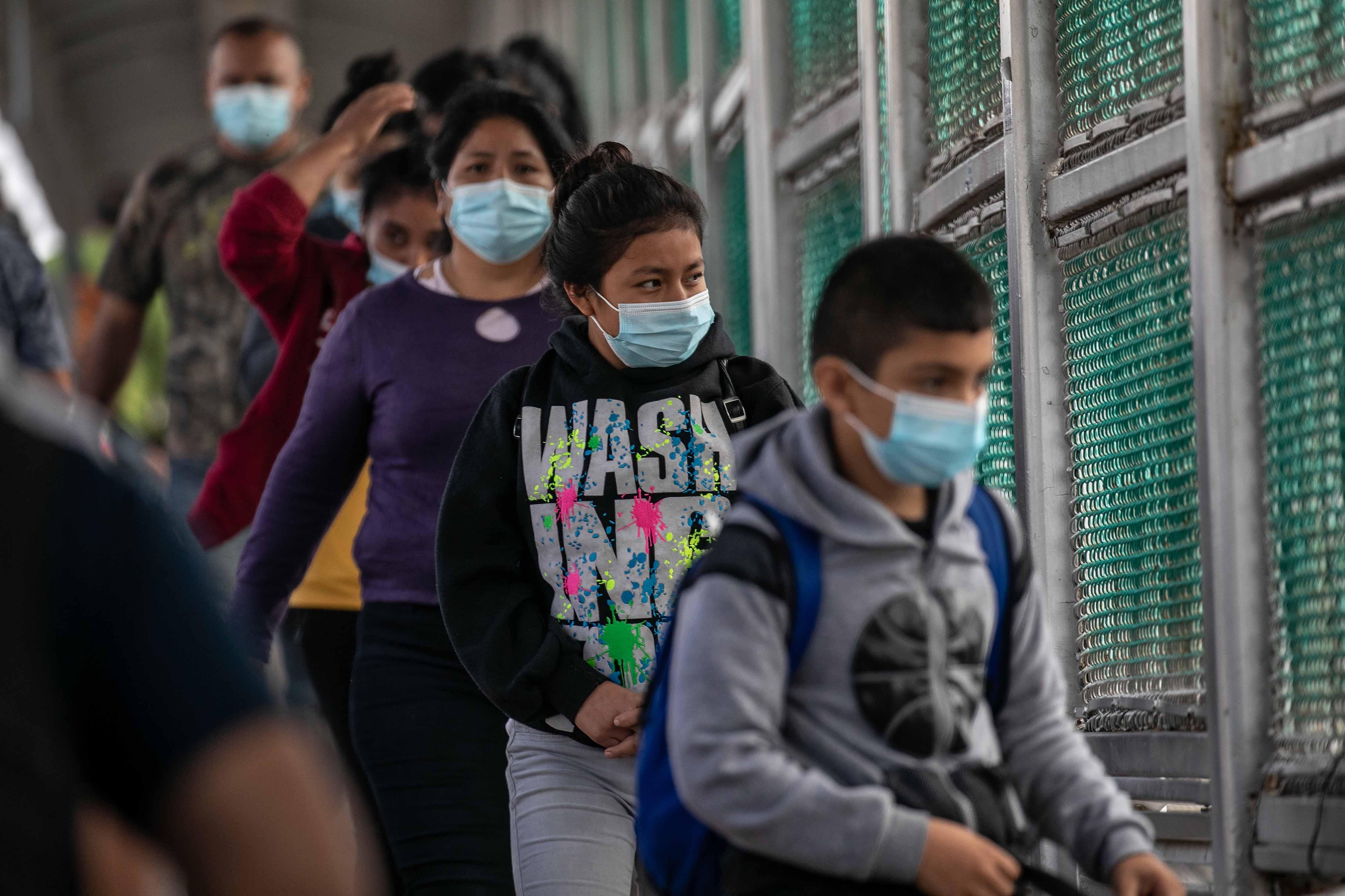 Deportees walk across a U.S.-Mexico border bridge from Texas into Mexico in Matamoros, Mexico.
