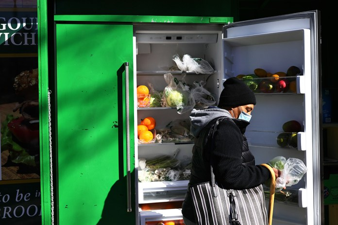 A person picks up food from a public refrigerator.