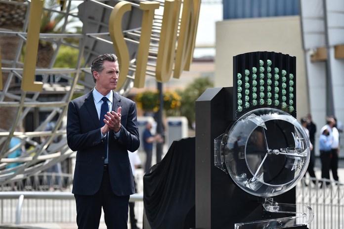 California Governor Gavin Newsom claps at a press conference.