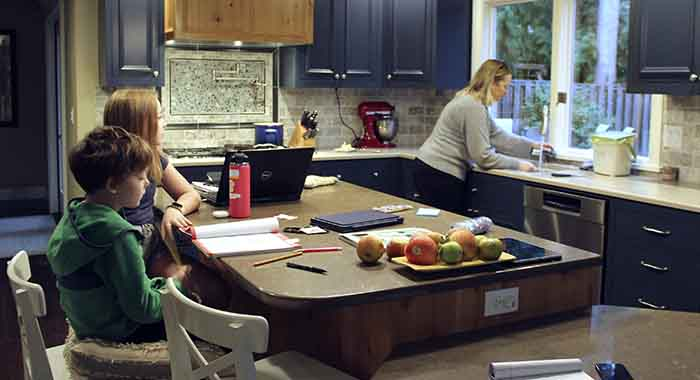 Charlie Dale works on his math notebook with help from his older sister Maddi as their mother cooks pancakes in their house in Lake Oswego, Ore.