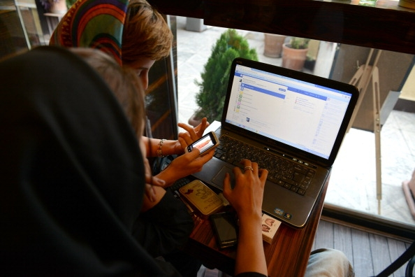Two girls use Facebook in a Tehran coffee shop