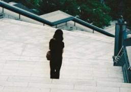 A solitary woman on the stairs in Akaska, Tokyo. Photo Noritoshi Hirakawa