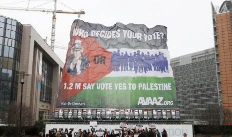 Para aktivis membentangkan bendera Palestina raksasa dalam aksi mendukung negara Palestina merdeka di luar Gedung Dewan Uni Eropa di Brussels, Senin (19/11). (Reuters/Francois Lenoir)