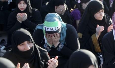Pengungsi Suriah melaksanakan shalat Idul Fitri di Amman, Yordania, Ahad (19/8). (Ali Jarekji/Reuters)