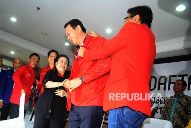 Calon gubernur DKI Jakarta Basuki Tjahaja Purnama mengenakan jaket pertai secara simbolis didampingi wakil gubernur Djarot Saifut Hidayat dan Ketua Umum PDIP Megawati Soekarnoputri saat mendaftar sebagai Pasangan calon gubernur dan wakil gubernur DKI Jakar