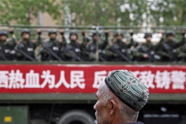 Seorang Muslim Uighur berada di depan militer yang patroli di wilayah Xinjiang.
