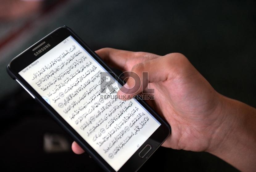 Seorang jamaah Masjid Agung Al-Azhar membaca ayat Alquran melalui ponsel usai menunaikan ibadah shalat Jumat, Jakarta Selatan, Jumat (19/6). (Republika/Rakhmawaty La'lang)