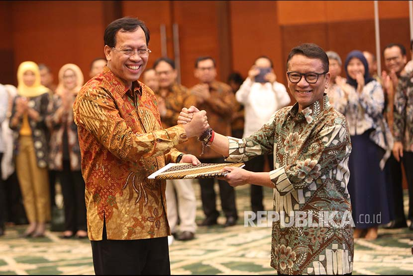 Direktur Jenderal Pajak Kementerian Keuangan yang baru  Robert Pakpahan (kiri) berjabat tangan dengan pejabat lama Ken Dwijugiasteadi saat serah terima jabatan di kantor Kementerian Keuangan (Kemenkeu), Jakarta, Kamis (30/11).