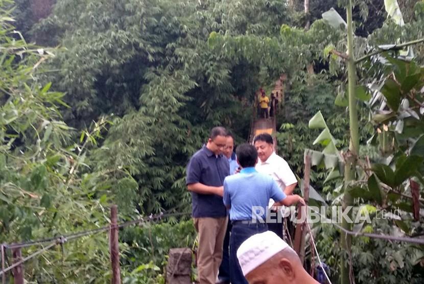 Gubernur DKI Jakarta Anies Baswedan memeriksa langsung kondisi jembatan gantung di kawasan Srengseng Sawah, Jakarta Selatan, Ahad (21/1) sore. Kondisi jembatan gantung tersebut sangat rawan dan mengkhawatirkan untuk dilewati.