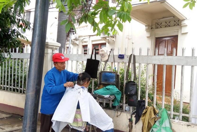 Hasanudin sedang merapikan rambut pelanggannya. Hasan merupakan satu-satunya tukang cukur DPR yang tersisa di kawasan sekitar Jatinegara.