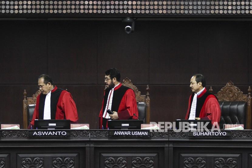 Ketua Majelis Hakim Mahkamah Konstitusi (MK) Anwar Usman (tengah) bersama Hakim MK Aswanto (kiri) dan Suhartoyo (kanan) meninggalkan ruangan seusai memimpin sidang pengujian UU No. 2 Tahun 2018 tentang perubahan kedua atas Undang-Undang Nomor 17 Tahun 2014 tentang MD3 di gedung MK, Jakarta, Selasa (3/4).